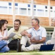 Royalty-Free Stock Photo: Adult students sitting on a campus lawn