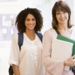 Two women with backpacks standing in a campus corridor — Stock Photo