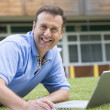 Man using laptop while lying in grass on campus — Stock Photo