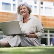 Senior woman using laptop on campus - Stock Photo