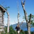 Man hiking up to a wooden cabin - Stock Photo