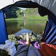 Woman lying in tent with a view of lake — Stock Photo