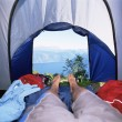Man lying in tent with a view of lake - Stock Photo