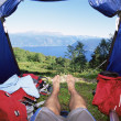 Man lying in tent with a view of lake - Stock fotografie
