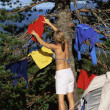 Stock Photo: Young womhanging out washing on tree next to campsite