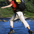 Hiker jumping from rock to rock while crossing river — Stock Photo #4754432