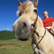 Young woman riding horse in rural setting - Stock Photo