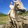 Young woman crossing a river by horse - Stock Photo