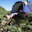 Camper relaxing at water's edge by tent — Stock Photo