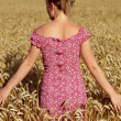 Rear view of young woman standing in wheatfield - Stockfoto