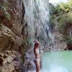 Woman in bikini standing under waterfall — Stock Photo