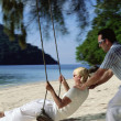 Man swinging woman on swing at beach, — Stock Photo