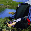 Young woman asleep in tent next to lake, — Stock Photo