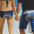 Rear view of young couple walking along beach with sandy bottoms — Stock Photo #4754575