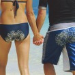 Rear view of young couple walking along beach with sandy bottoms - Stock Photo