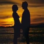 silhuett av par står ansikte mot ansikte på stranden vid solnedgången — Stockfoto