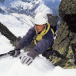 Mountaineer using ice axe to climb steep slope — Stock Photo #4754627