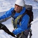 Young man mountain climbing on snowy peak — Stock Photo