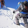 Young men mountain climbing on snowy peak — ストック写真