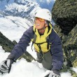 Mountaineer climbing a steep slope. - Stock Photo