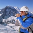 Young man warming hands on mountain peak - Stock Photo