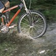 Mountain biker crossing stream - Stock Photo