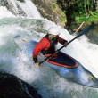 Young woman kayaking in rapids — Stock Photo
