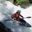 Young woman kayaking down waterfall - Stockfoto