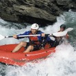 Stock Photo: Two paddling inflatable boat down rapids