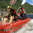 Two paddling inflatable boat down rapids — Stock Photo