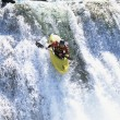 Young man kayaking down waterfall - Stok fotoğraf