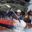 Two paddling inflatable boat down rapids - Stok fotoğraf