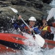 Two paddling inflatable boat down rapids - Stock Photo