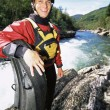Stock Photo: Mstanding with raft beside river