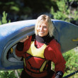 Young woman carrying kayak - Stockfoto