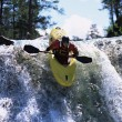 Young man kayaking down waterfall - Stock Photo