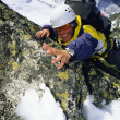 Mountaineer climbing snowy rock face — Stock Photo
