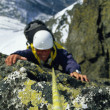 Mountaineer scaling snowy rock face - Stok fotoraf