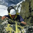 Mountaineer scaling snowy rock face - Stock Photo