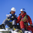 Stock Photo: Young men mountain climbing on snowy peak