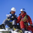 Young men mountain climbing on snowy peak — Stock Photo
