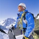 Young man mountain climbing on snowy peak — Stock Photo #4754805