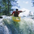 Young man kayaking on waterfall - Stock Photo