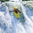 Young man kayaking down waterfall - Stockfoto