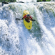 Stock Photo: Young mkayaking down waterfall