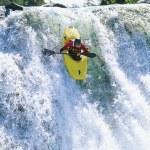 Young man kayaking down waterfall — Stock Photo
