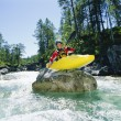 Kayaker perched on boulder in river - Stock Photo