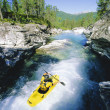 Young man kayaking in river - Stock Photo
