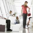 Passengers waiting in airport departure lounge - Stock Photo