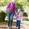 Mother and daughter walking along autumn path — Stock Photo